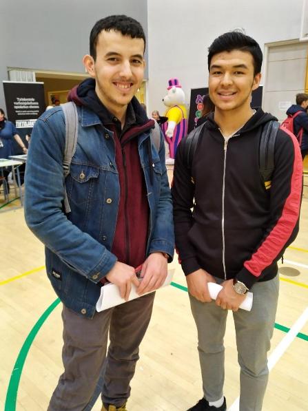 Kaksi poikaa hymyilee kameralle koulun liikuntasalissa.