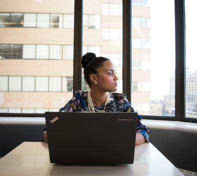 Koronakriisin vaikutuksia maahanmuuttajien elämään Suomessa -blogikirjoituksen kuvvituskuva, jossa nainen istuu tietokoneella ja katselee oikealle.