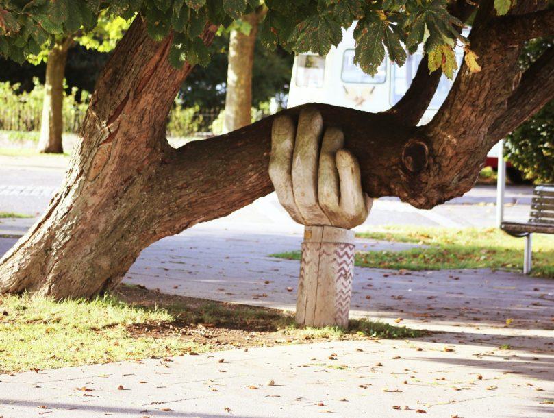 Lisää tukea -blogin kuvituskuva. Kuvassa puun runko, jota pitelee veistoskäsi.