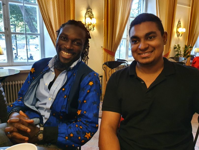 Two man sitting on a table and smiling.