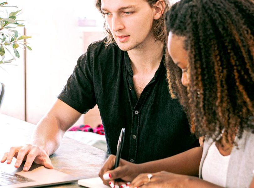 Kaksi henkilöä iststuu pöydän ääressä. Toinen kirjoittaa läppärillä ja toinen käsin paperille.