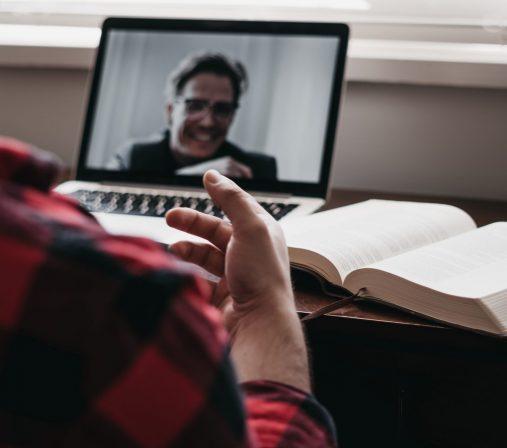 Henkilö puhuu tietokoneelle, jossa on käynnissä videopalaveri. Blogitekstin yritysvalmennus kuvituskuva.