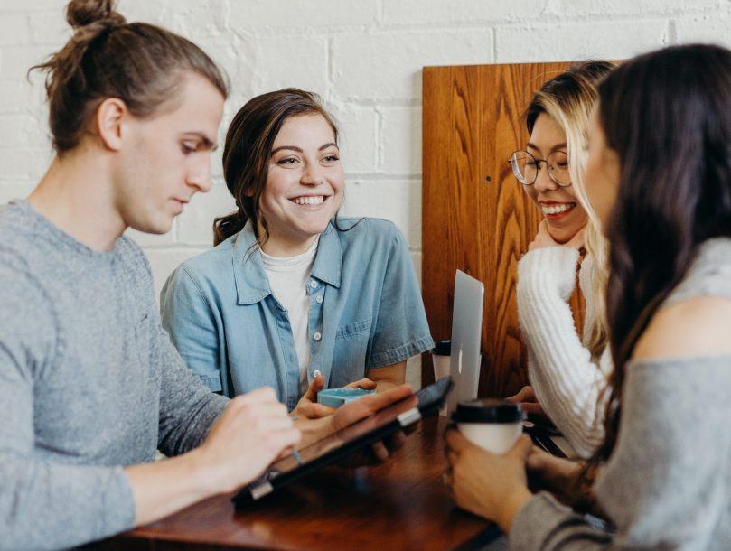 Neljä henkilöä seisoo pöydän äärellä ja keskustelee iloisesti.